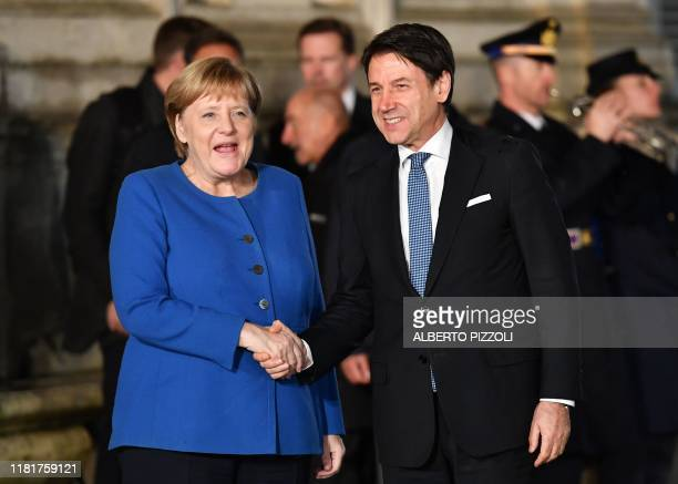 Italy's Prime Minister Giuseppe Conte greets German Chancellor Angela Merkel upon her arrival for their meeting at Villa Pamphili in Rome on November...