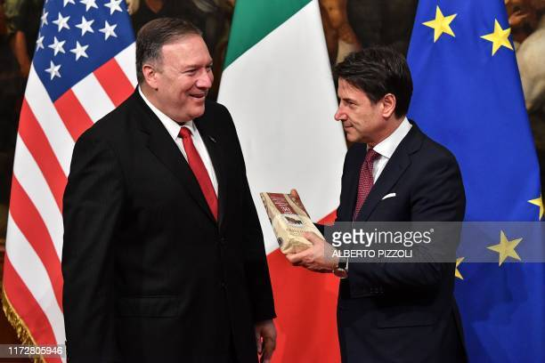 Italy's Prime Minister Giuseppe Conte holds a package of Parmesan cheese handed to him by US Secretary of State Mike Pompeo after it was gived to...