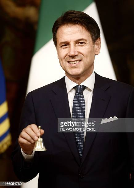 Italy's Prime Minister Giuseppe Conte rings the silver bell during the bell ceremony marking the start of the new Cabinet's first meeting on...