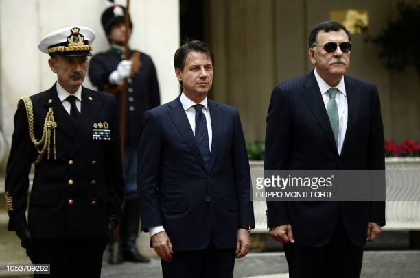 Italy's Prime Minister Giuseppe Conte satands past his Libyan counterpart Fayez al-Sarraj before a meeting at the Palazzo Chigi in Rome on October...