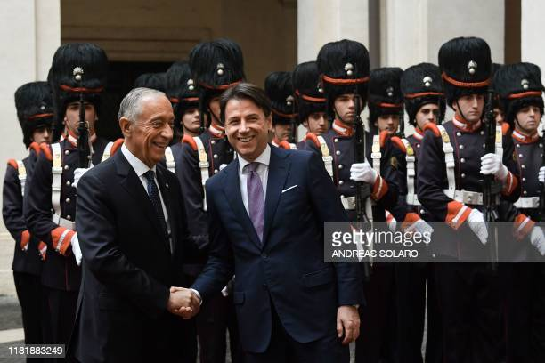 Italy's Prime Minister Giuseppe Conte shakes hand with Portugal's President Marcelo Rebelo de Sousa upon his arrival for their meeting on November...
