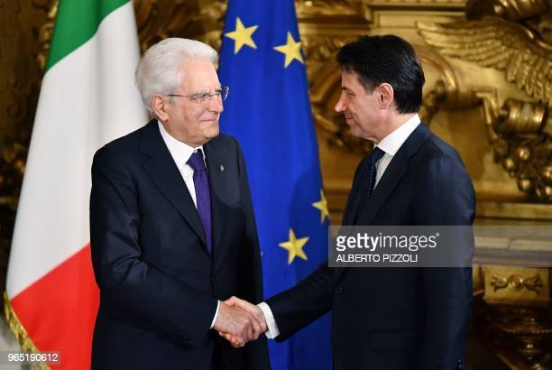 TOPSHOT Italys Prime Minister Giuseppe Conte shakes hands with Italy's President Sergio Mattarella during the swearing in ceremony of the new...