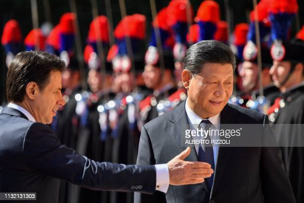 TOPSHOT Italys Prime Minister Giuseppe Conte shows the way to China's President Xi Jinping during a welcoming ceremony upon Xi Jinping's arrival for...