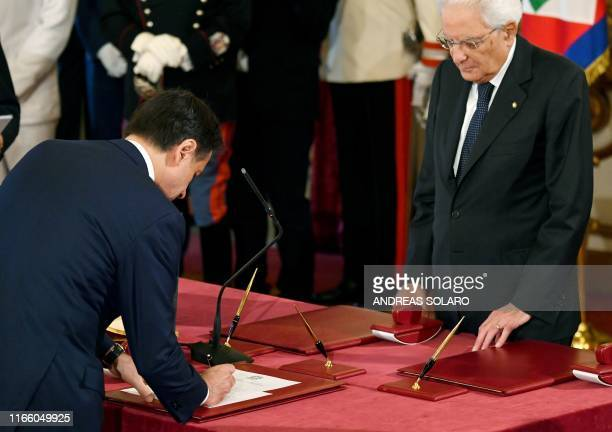 Italy's Prime Minister Giuseppe Conte signs an oath of office as Italy's President Sergio Mattarella looks on during a swearing-in ceremony at the...