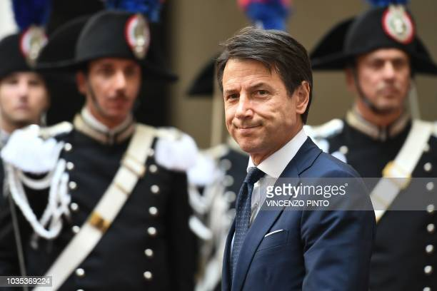 Italy's prime minister Giuseppe Conte walks past a Guard of Honor of Carabinieri police officers as he arrives to welcome Austria's chancellor at...