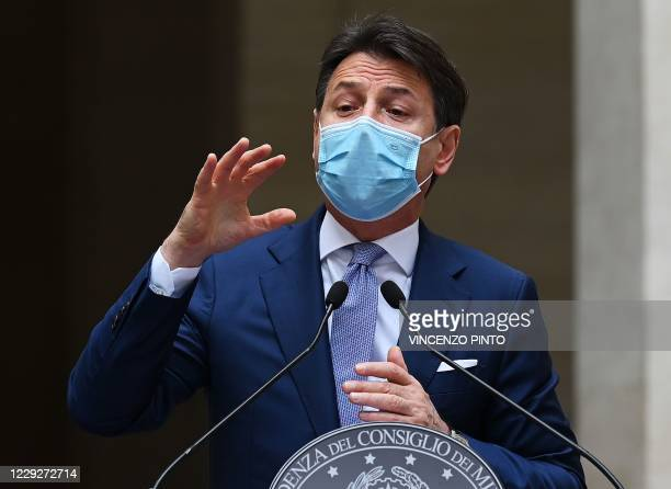 Italy's Prime Minister Giuseppe Conte, wearing a protective facemask, gestures as he speaks during a press conference for the newly adopted measures...