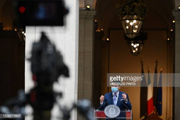 Italy's Prime Minister Giuseppe Conte, wearing a protective facemask, speaks during a press conference for the newly adopted measures to fight...