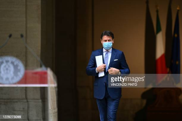 Italy's Prime Minister Giuseppe Conte, wearing a protective facemask, arrives for a press conference for the newly adopted measures to fight against...