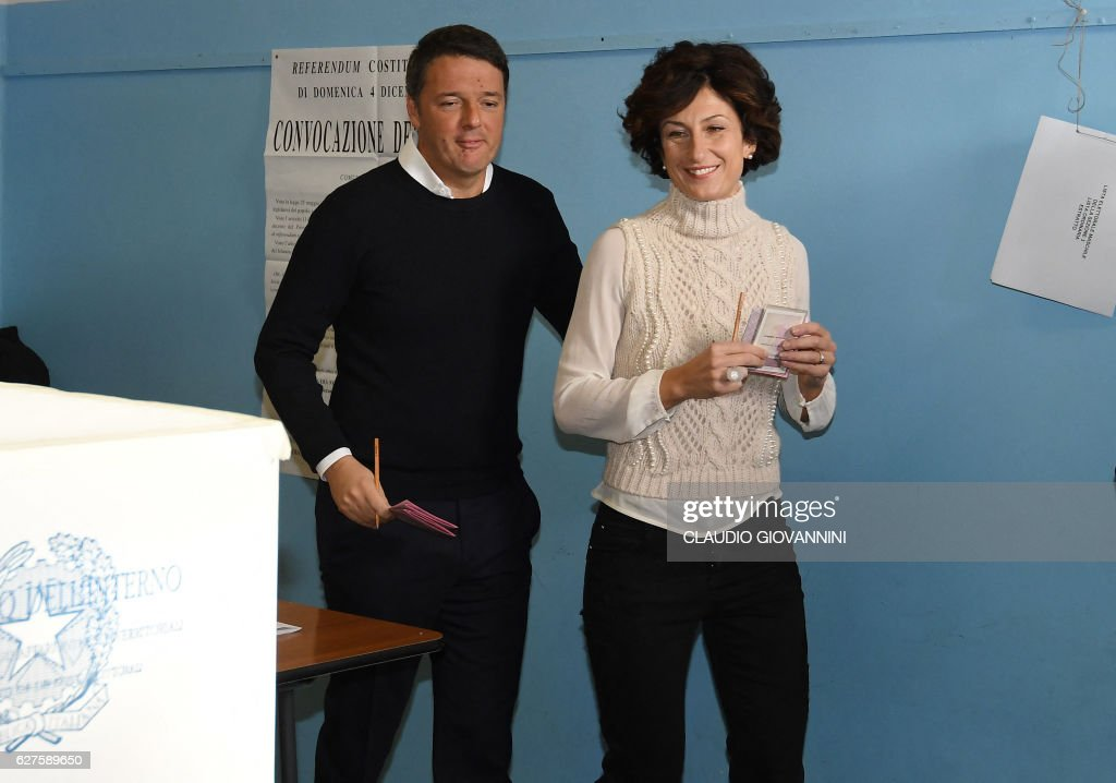 Italy's Prime Minister Matteo Renzi (L) and his wife Agnese Landini arrive to vote for a referendum on constitutional reforms, on December 4, 2016 at a polling station in Florence. Italians began voting today in a constitutional referendum on which reformist Prime Minister Matteo Renzi has staked his future. Under Renzi's proposed reform, a body of 315 directly-elected and five lifetime lawmakers will become one with only 100 members, mostly nominated by the regions. The body would also be stripped of most of its powers to block and revise legislation, and to unseat governments. GIOVANNINI