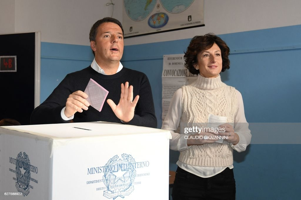Italy's Prime Minister Matteo Renzi and his wife Agnese Landini vote for a referendum on constitutional reforms, on December 4, 2016 at a polling station in Florence. Italians began voting today in a constitutional referendum on which reformist Prime Minister Matteo Renzi has staked his future. Under Renzi's proposed reform, a body of 315 directly-elected and five lifetime lawmakers will become one with only 100 members, mostly nominated by the regions. The body would also be stripped of most of its powers to block and revise legislation, and to unseat governments. GIOVANNINI