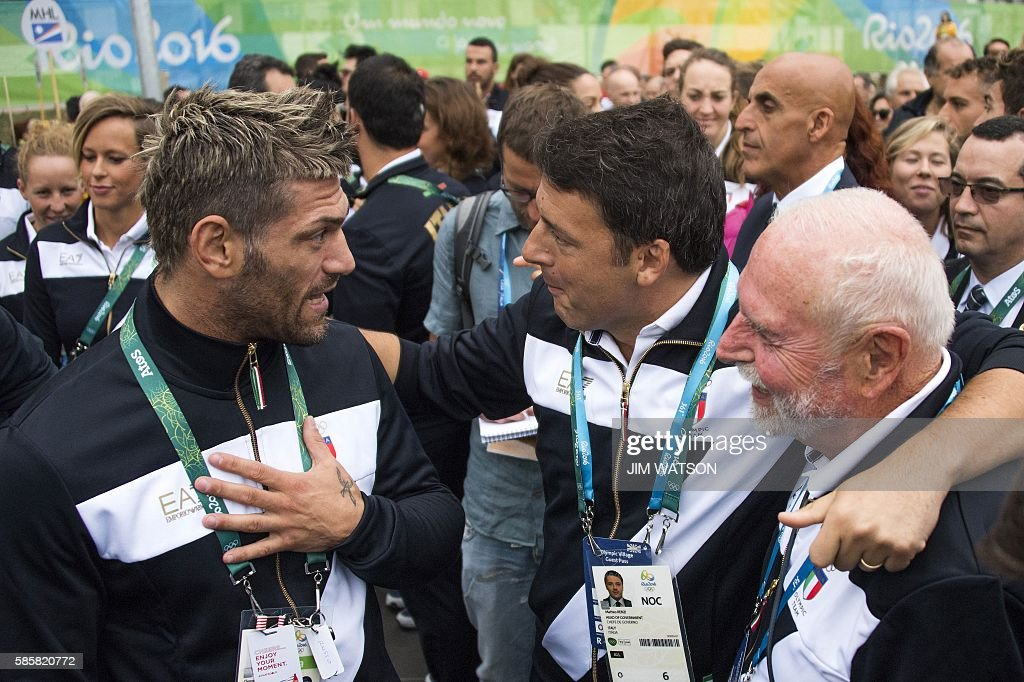 TOPSHOT - Italy's Prime Minister Matteo Renzi (C) speaks with members of the Italian National Olympic Team during a welcoming ceremony at the Olympic Village ahead of the Rio 2016 Olympic Games in Rio de Janeiro, on August 4, 2016. / AFP / JIM