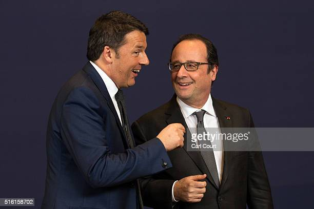 Italy's Prime Minister Matteo Renzi talks with France's Prime Minister Francois Hollande after a group photograph on the first day of an EU summit at...