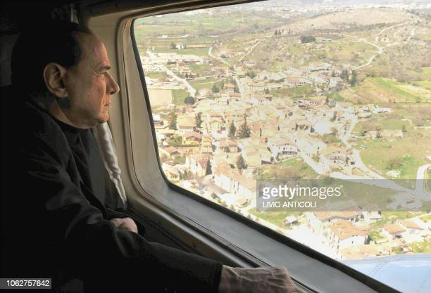 Italy's Prime Minister Silvio Berlusconi flies over the area of L'Aquila, following an earthquke on April 6, 2009. A violent earthquake jolted...