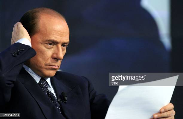 Italy's Prime Minister Silvio Berlusconi looks at his notes before taking part in a political talk show on an Italian national network, 11 February...