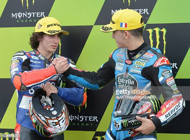 Italy's rider Niccolo Antonelli pole is congratulated by third Spanish's rider Aron Canet after the Moto3 qualifying cession of the French...