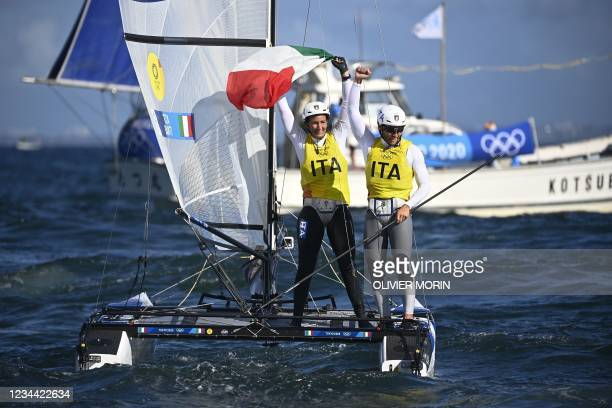 Italy's Ruggero Tita and Caterina Banti celebrate winning the gold medal after the mixed multihull Nacra 17 foiling race during the Tokyo 2020...