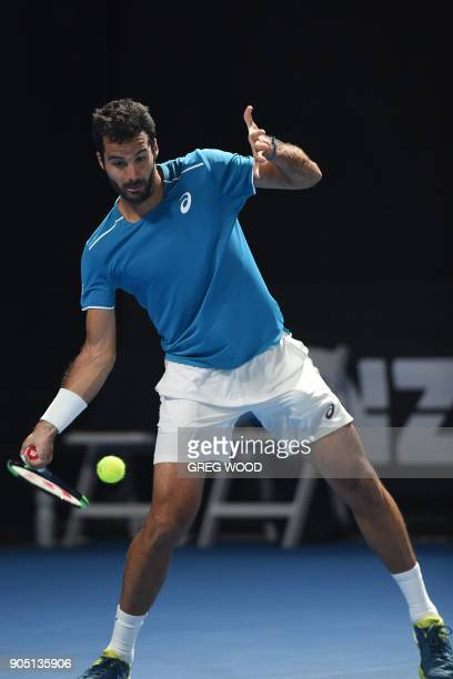 Italy's Salvatore Caruso plays a forehand return to Tunisia's Malek Jaziri during their men's singles first round match on day one of the Australian...
