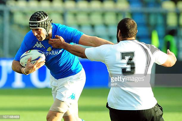 Italy's Santiago Dellape palms off Fiji's Deacon Manu during their the Test match Italy against Fiji on November 27 2010 at the Braglia stadium in...