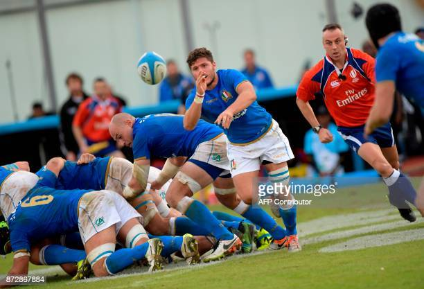 Italy's scrumhalf Marcello Violi is watched by Ireland's referee John Lacey as he releases the ball after a scrum during the international rugby...