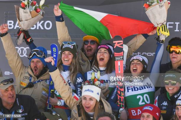 Italy's second placed Marta Bassino first placed Elena Curtoni and third placed Frederica Brignone celebrate with their team on the podium after the...