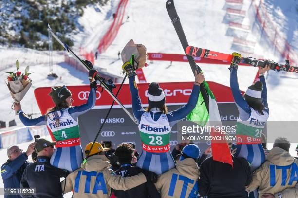 Italy's second placed Marta Bassino first placed Elena Curtoni and third placed Frederica Brignone celebrate after the ladies' downhill event at the...
