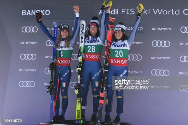 Italy's second placed Marta Bassino first placed Elena Curtoni and third placed Frederica Brignone celebrate on the podium after the ladies' downhill...