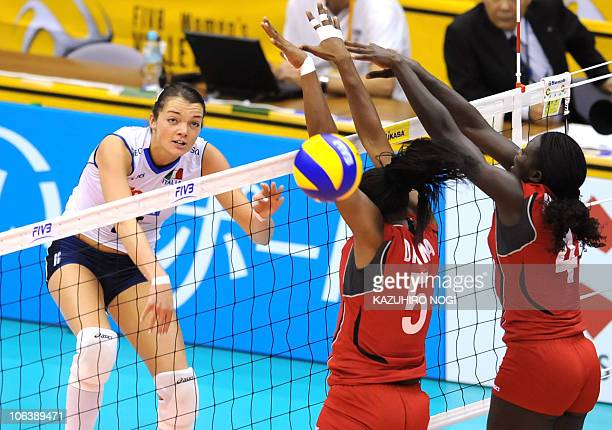 Italy's Serena Ortolani spikes the ball past Kenya's Diana Khisa and Esther Mwombe during their first round match of the world women's volleyball...