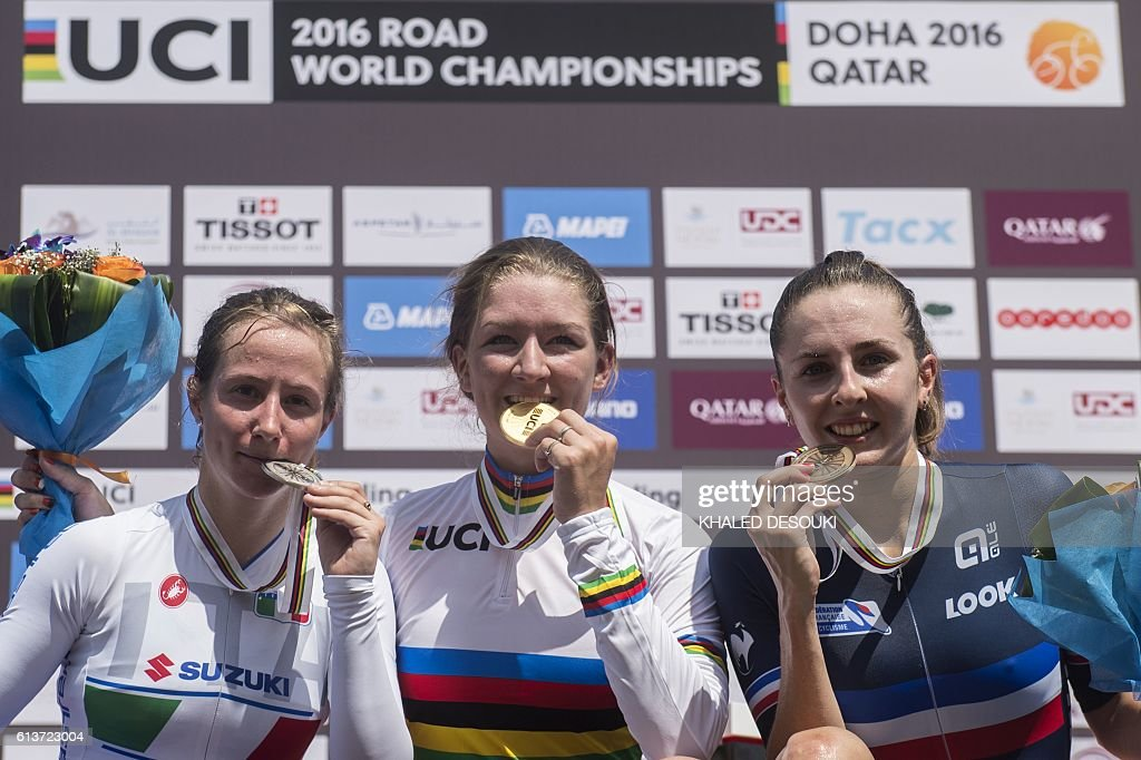 Italy's silver medallist Lisa Morzenti, gold medallist Karlijn Swinkels of the Netherlands, and France's bronze medallist Juliette Labous celebrate on the podium at the end of the women's junior individual time trial event as part of the 2016 UCI Road World Championships on October 10, 2016, in the Qatari capital Doha / AFP / KHALED