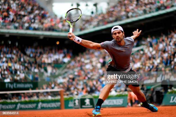 TOPSHOT Italy's Simone Bolelli plays a backhand return to Spain's Rafael Nadal during their men's singles first round match on day three of The...