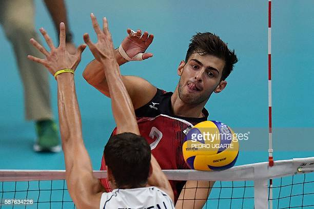 Italy's Simone Giannelli attempts to block a shot from US Aaron Russell during the men's qualifying volleyball match between Italy and the USA at the...