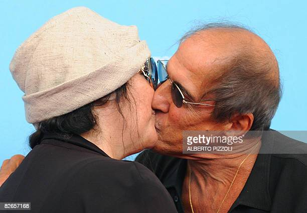 Italy's singer and director Adriano Celentano kisses his wife Claudia Mori during the photocall of his movie Yuppi Du at the 65th Venice...