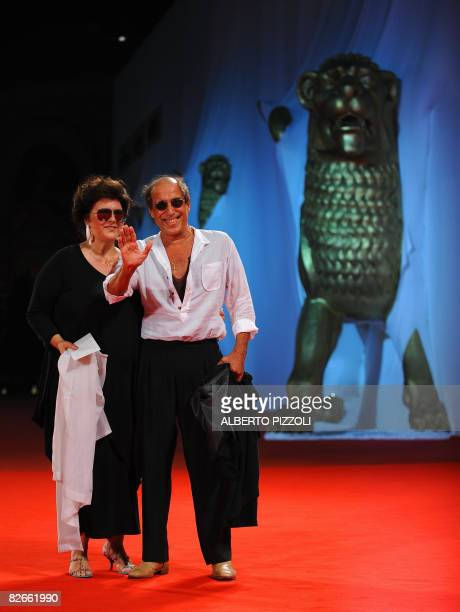 Italy's singer and director Adriano Celentano poses with his wife Claudia Mori before the screening of his movie Yuppi Du at the 65th Venice...