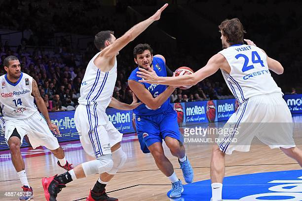 Italy's small forward Alessandro Gentile dribbles his way through Czech Republic's power forward Petr Benda and Czech Republic's power forward Jan...