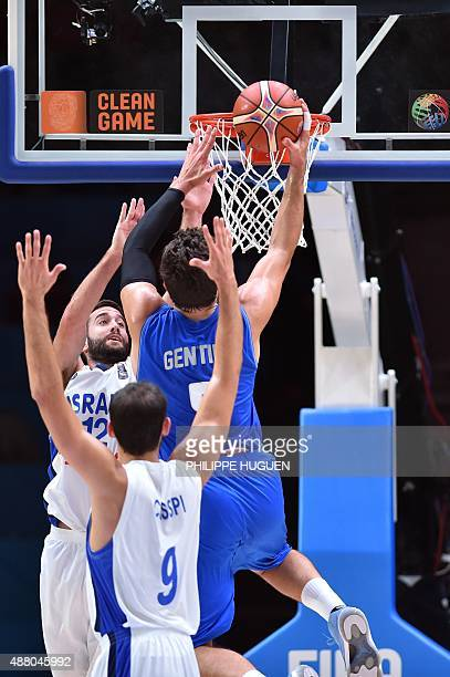 Italy's small forward Alessandro Gentile goes to the basket despite Israel's point guard Yogev Ohayon and Israel's small forward Omri Casspi during...