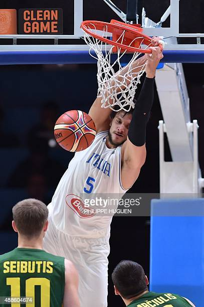Italy's small forward Alessandro Gentile hangs onto the rim after slamming a dunk during the round of 8 basketball match between Italy and Lithuania...