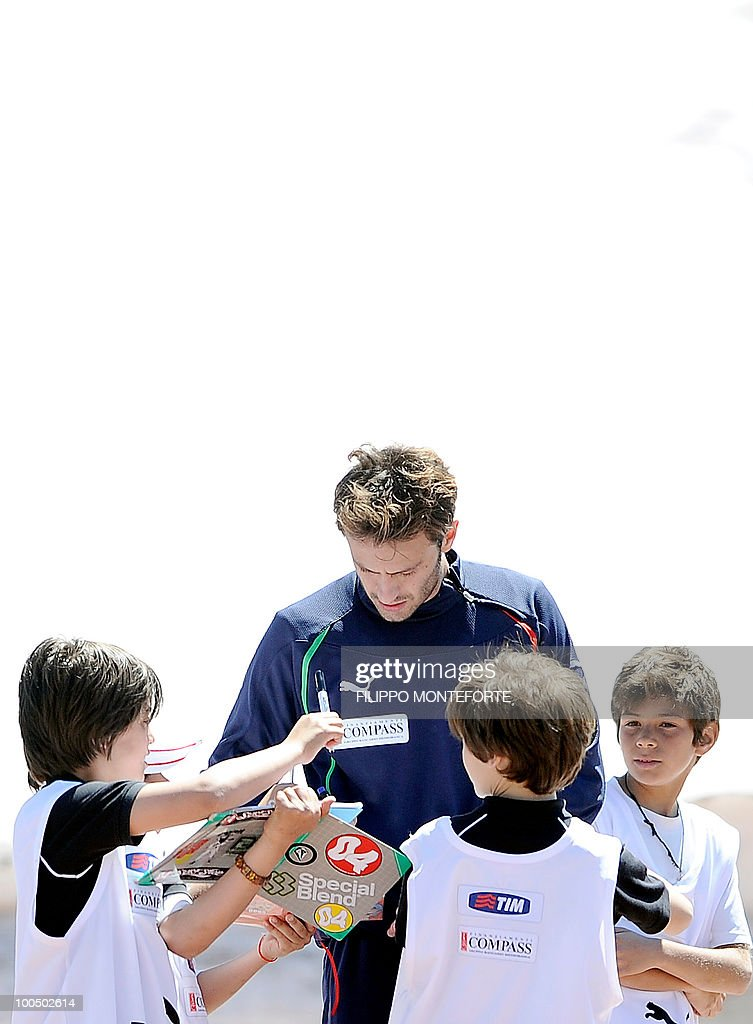 Italy's soccer team's forward Alberto Gilardino (C) signs an autograph to a young supporter during a training session in Sestriere on May 25, 2010. The Italian team stays for a training session in the mountains of Sestriere before the FIFA World Cup 2010 in South Africa .AFP PHOTO / Filippo MONTEFORTE
