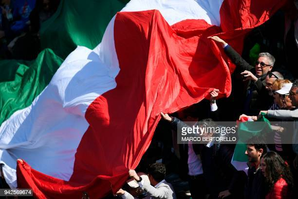 Italy's supporters wave a Italian national flag during the Davis Cup tennis quarter final match Italy vs France on April 6 2018 at the Valletta...