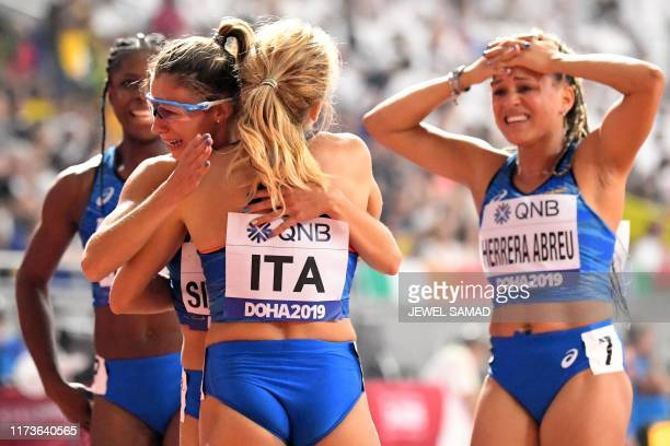 Italy's team members celebrate after competing in the Women's 4x100m Relay heats at the 2019 IAAF Athletics World Championships at the Khalifa...