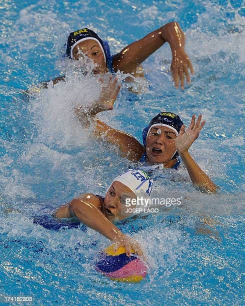 Italy's Teresa Frassinetti vies with Kazakhstan's Aizhan Akilbayeva and Assel Jakayeva during their preliminary round match of the women's water polo...