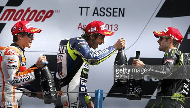Italy's Valentino Rossi celebrates on the podium with Marc Marquez and Cal Crutchlow after winning the Dutch MotoGP in Assen on June 29 2013 The...