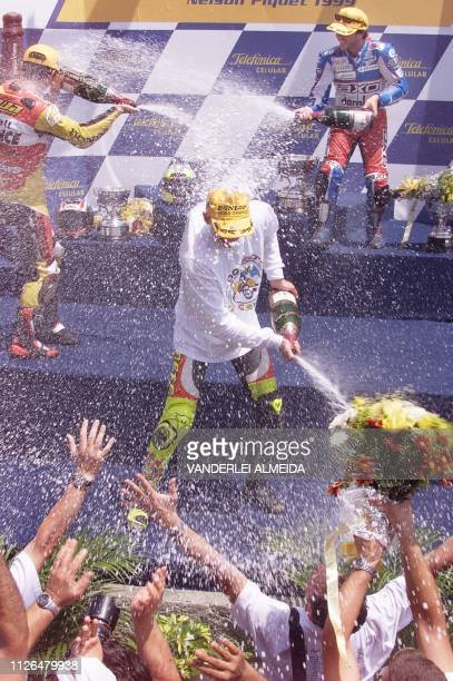 Italy's Valentino Rossi of team Aprilia celebrates with Tohru Ukawa of the Honda Shell team and Loris Capirossi of team Honda Elf on the podium 24...