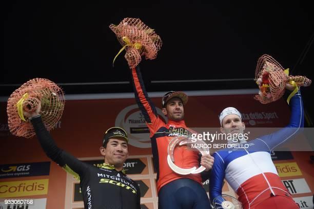 Italy's Vincenzo Nibali of team Bahrain winner poses on the podium with Australian Caleb Ewan of team Mitchelton Scott second and France's Arnaud...