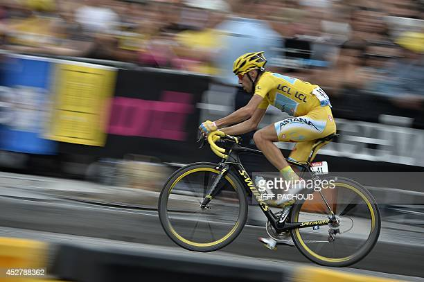 Italy's Vincenzo Nibali, wearing the overall leader's yellow jersey, rides in the pack on the Champs-Elysees avenue during the 137.5 km twenty-first...