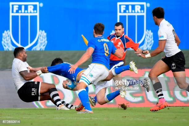 Italy's winger Leonardo Sarto is tackled by Fiji's winger Timoci Nagusa during a rugby union test match between Italy and Fiji at the Angelo...