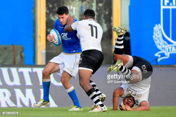 Italy's winger Leonardo Sarto vies with Fiji's wing Timoci Nagusa during a rugby union test match between Italy and Fiji at the Angelo Massimino...