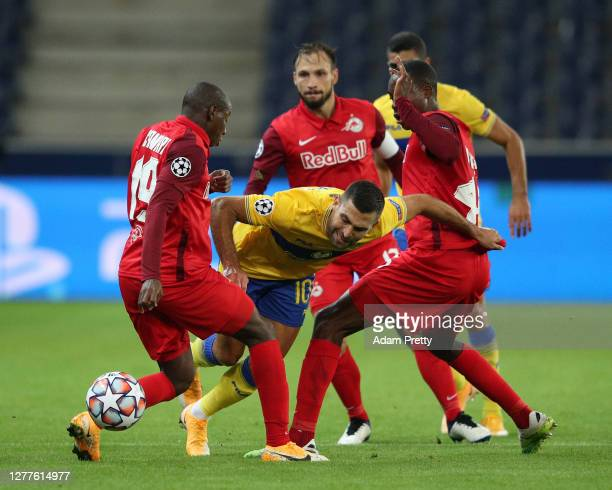 Itay Shechter of Maccabi Tel-Aviv is challenged by Mohamed Kamara and Enock Mwepu of RB Salzburg during the UEFA Champions League Play-Off second leg...