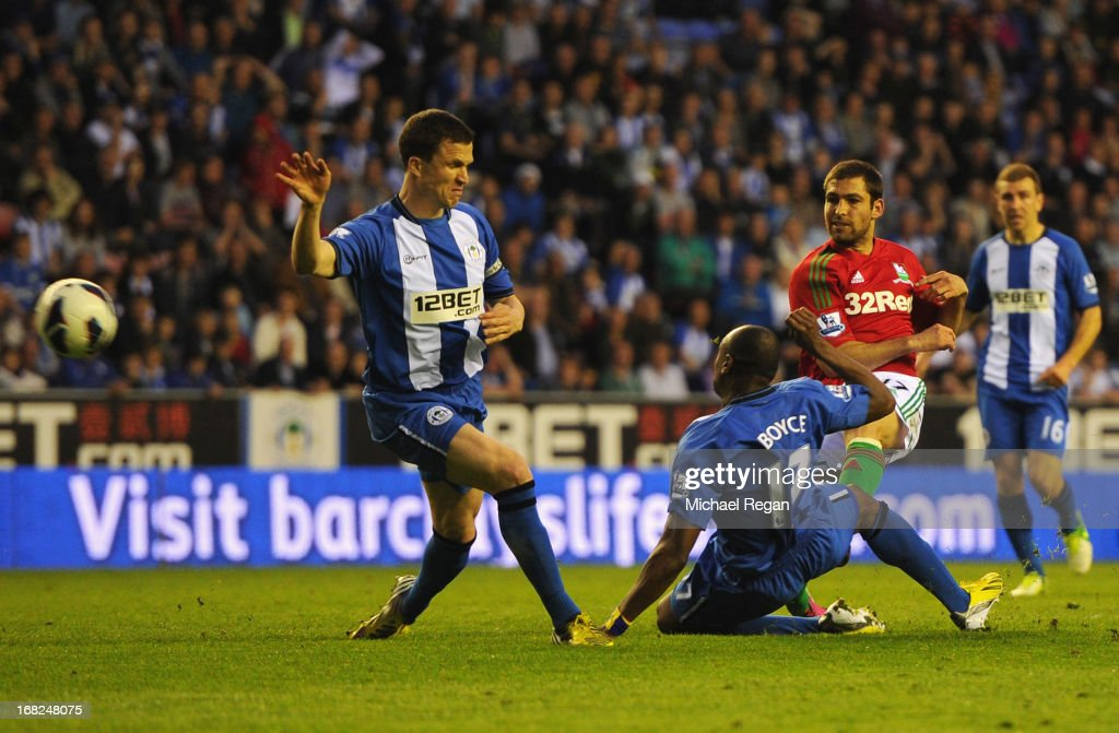 Itay Shechter of Swansea City (2R) shoots past Gary Caldwell (L) and Emmerson Boyce of Wigan Athletic (17) to score their second goal during the Barclays Premier League match between Wigan Athletic and Swansea City at DW Stadium on May 7, 2013 in Wigan, England.