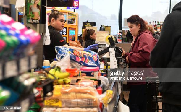 Items are piled up at the checkout counter of a Ralph's Supermarket in North Hollywood, California on March 19 as people continue shopping food and...