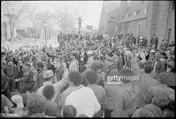"""Ithaca, New York: Campus Guns. Onlookers raise clenched fists in a """"Black Power"""" salute as armed Negro students walk along the Cornell University..."""