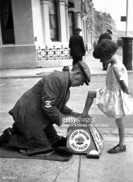 Itinerant shoeblack polishing a young girl's shoe c 1920s